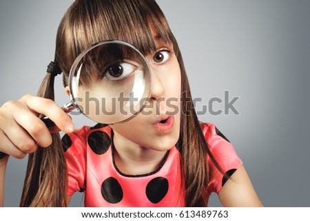 amazed child girl looking through magnifying glass, searching concept