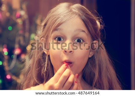 Amazed child looking at camera during Christmas holidays after receiving Christmas gift