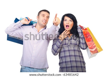 Amazed couple at shopping,man pointing up to promotions and woman being very surprised isolated on white background - stock photo