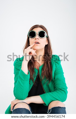 Amazed cute young woman in green jacket and round sunglasses sitting and looking up over white background - stock photo