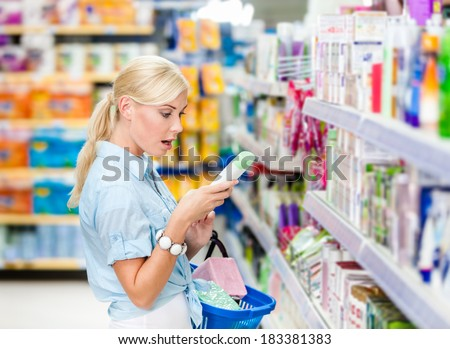 Amazed girl at the store choosing cosmetics among the great variety of products. Concept of consumerism, retail and purchase