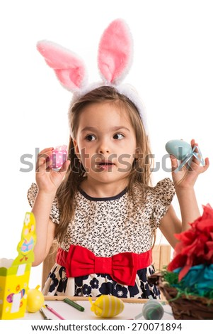 Amazed girl with bunny ears holding Easter eggs and looking at the pink one isolated on white background - stock photo