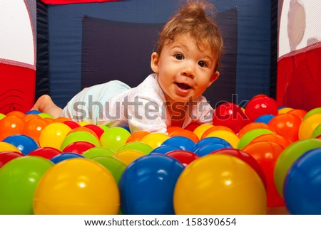 Amazed happy baby laying on colorful balls in playpan - stock photo