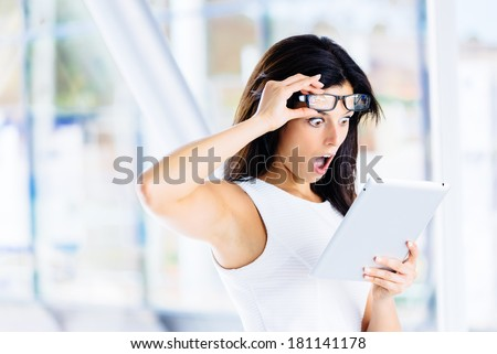 Amazed jaw dropped woman reading on digital tablet. Modern casual businesswoman with mouth open and surprise expression. - stock photo