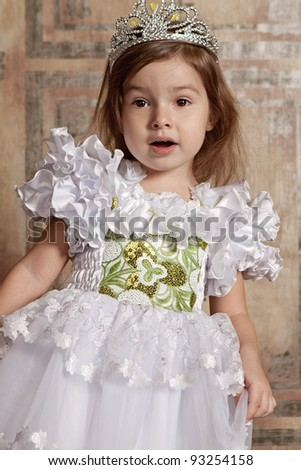 amazed little cute girl in white dress with a tiara on her head - stock photo