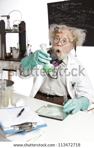 Amazed mad senior scientist in lab reacts to foaming green liquid overflowing beaker. Frizzy grey hair, round glasses, lab coat, aqua rubber gloves, blank blackboard, vertical, high key, copy space. - stock photo