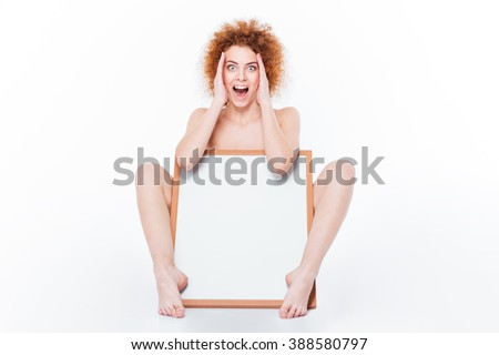 Amazed naked woman sitting with blank board isolated on a white background