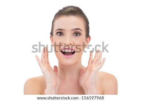 Amazed natural brown haired model raising her hands on white background