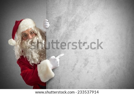 Amazed santa claus indicates a blank billboard - stock photo