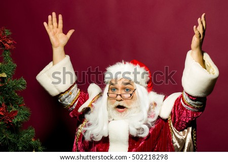 Amazed santa claus man in eyeglasses and red Christmas suit puts up hands with surprise near xmas tree