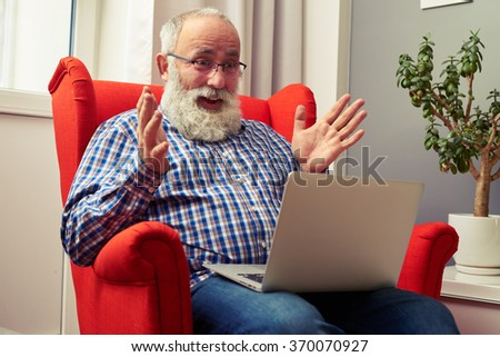 amazed senior man sitting on the chair and looking at laptop