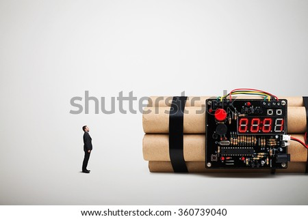 amazed small man looking at big bomb with timer over white background - stock photo
