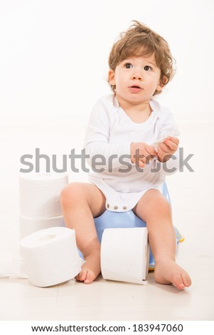 Amazed toddler boy on potty looking up and thinking - stock photo