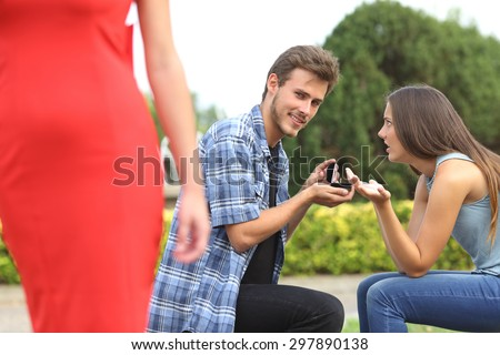 Amazed unfaithful man looking another girl during marriage proposal and his girlfriend is angry - stock photo