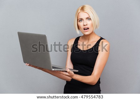 Amazed unhappy young woman using laptop over gray background