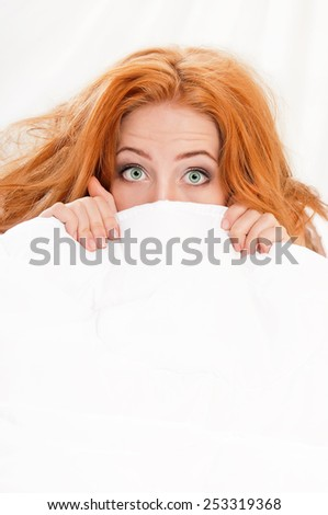 Amazed woman is lying in bed under blanket and looking at camera - stock photo