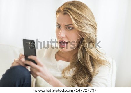 Amazed young Caucasian woman looking at mobile phone while relaxing on sofa