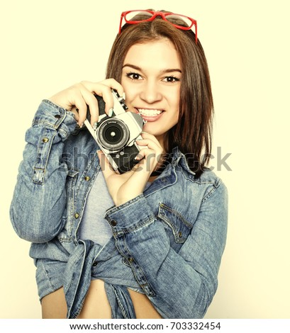 Amazed young pretty woman holding camera over white  background.
