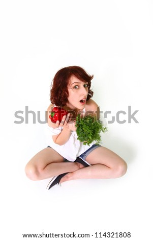 Amazed young woman sitting and holding pepper, parsley, dill - stock photo