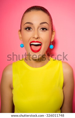 Amazed young woman with opened mouth. Pink background. - stock photo