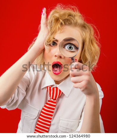 Amazedly funny woman with magnifier, isolated on red background - stock photo