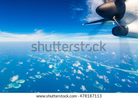 Amazing aerial view on the island on Maldives from above with a detail of a plane.