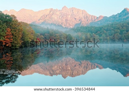 Amazing autumn lake scenery of Kagami Ike (Mirror Pond) in morning light with symmetric reflections of colorful fall foliage on smooth water & rugged Togakushi Mountain in background in Nagano, Japan - stock photo