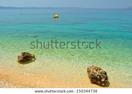 Amazing beach with two big stones and crystal clear water near Tucepi, Croatia - stock photo
