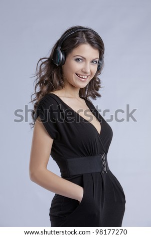 amazing beautiful girl with headphones in black dress at studio shooting - stock photo