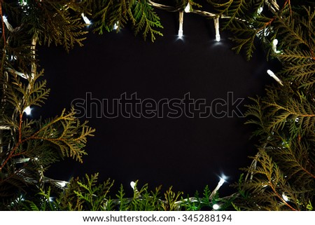 amazing beautiful green fir or cedar and unique christmas golden vintage garland lights on black background - stock photo