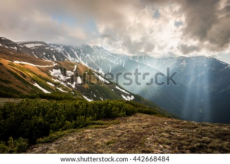 Amazing, beautiful landscape in the Carpathian mountains in Romania near the Urlea peak with brilliant, misty sunbeams, cloudy sky, green forest and idyllic highland atmosphere - stock photo