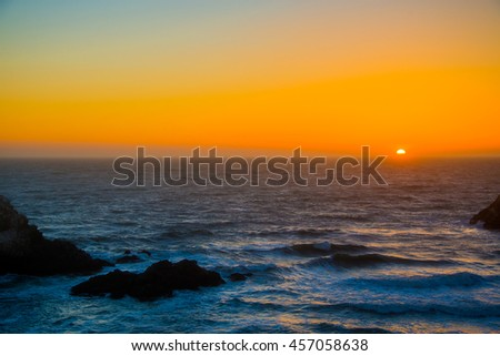 Amazing beautiful sunset view by the Pacific ocean near San Francisco. Sun sets down the horizon. - stock photo