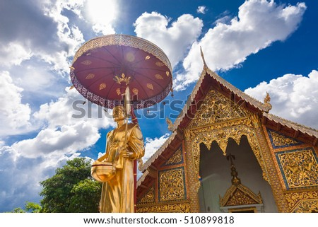 Amazing beautiful view golden Buddhist statue monk on scenery nature blue background in one of the most popular tourist landmarks in northern Thailand / Thailand Temple Wat Prasingh / Thailand