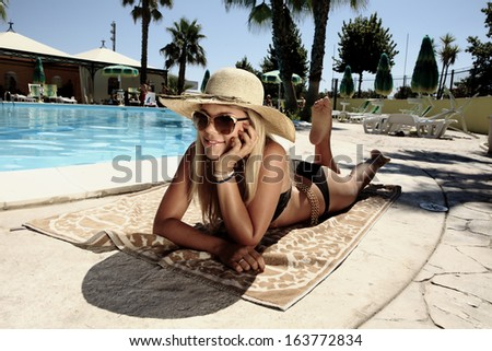 Amazing Blonde girl Relaxing in the pool with hat and sunglasses - stock photo