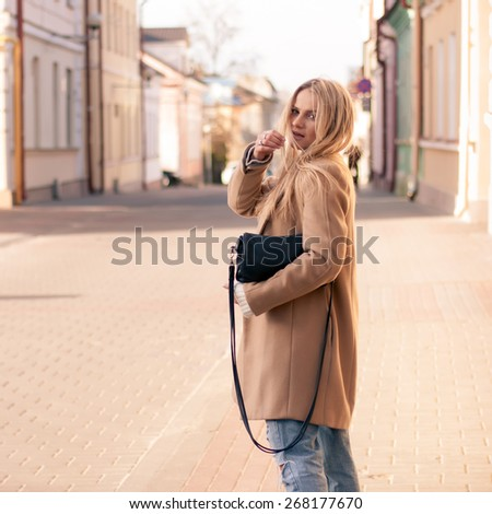Amazing blonde girl walking alone on the road in old european city. Dressed on ripped jeans and coat - stock photo