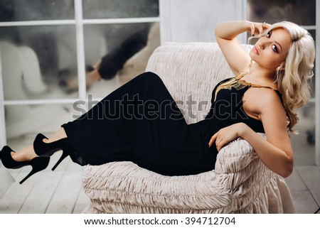 Amazing blonde woman beautiful sexy woman with chic long blond curly hair in an elegant black dress sitting in a luxury white chair with gold-plated jewelry stylish manicure on nails and trendy makeup - stock photo