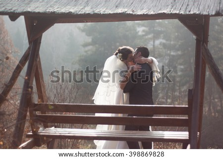 Amazing Bride and Groom Kissing near arbor in the park. Multi ethnic couple : man of peruvian ethnicity (latin american and hispanic ethnicity) and woman of caucasian ethnicity. - stock photo