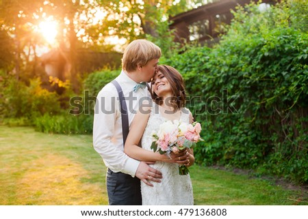 Amazing bride with her tender bouquet and handsome groom