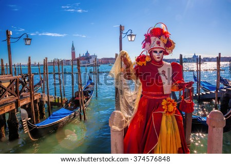 Amazing carnival mask against gondolas in Venice, Italy
