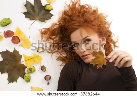 amazing close up of a pretty red haired woman with autumn leaves