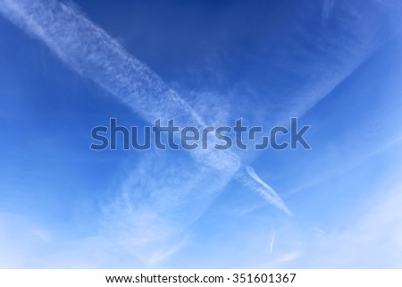 Amazing cloudscape with two aircraft crossed tracks in a blue sky