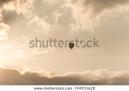 Amazing colors of sunrise with sunbeams over clouds and hot air balloon silhouette - stock photo