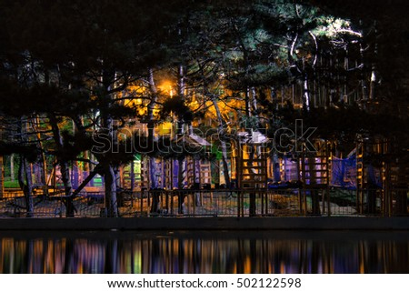 amazing dark night park view with small houses ladders roads and steps colorful lighting