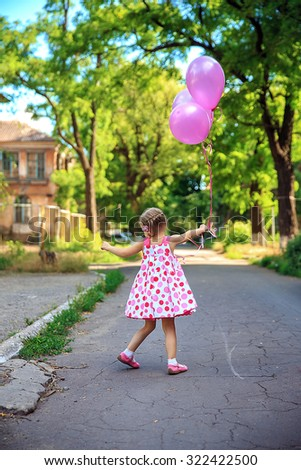 Amazing emotions of a beautiful little girl playing with the air balloons in the courtyard.