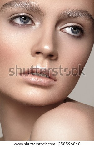 Amazing fashion winter make-up with bright shiny skin, pale lips, sparkles eyebrows. Beautiful christmas celebratory woman look - stock photo