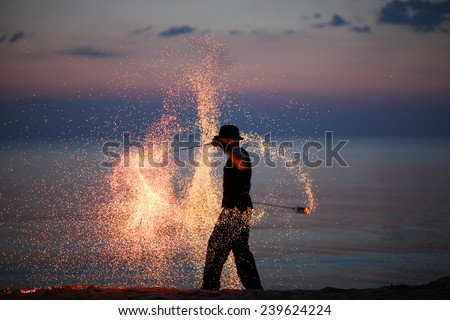 Amazing fire dance on the beach; fire sparks - stock photo