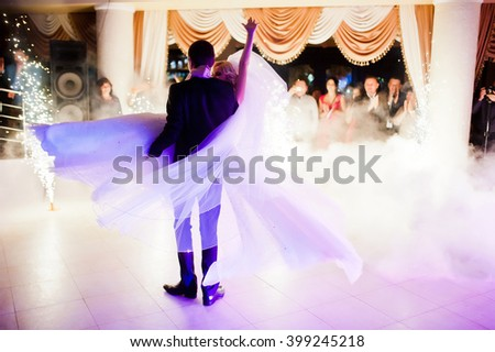 Amazing first wedding dance of newlyweds on low pink light and heavy smoke with fireworks.  Photo with noise - stock photo