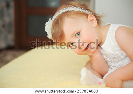 amazing girl sitting on bed with hand on cheek - stock photo