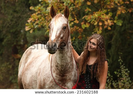 Amazing girl standing next to the appaloosa horse in autumn
