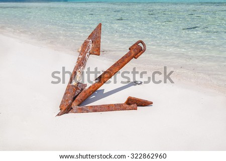 amazing gorgeous closeup view of old abandoned vintage ship rusty anchor, sitting on white sand beach against ocean background - stock photo